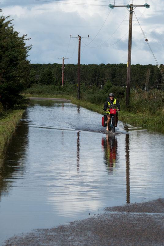 Wir radeln mit nackten Füßen durch überflutete Straßen zwischen Elgin und Banff